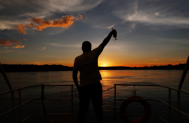 Silhouette of Wildlife photographer Clement Kiragu holding up a cocktail glass on a boat on the Zambezi river in Zambia